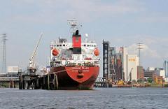 Das Tankschiff SICHEM PEACE liegt am Anleger in der Rethe - im Hintergrund Industriegebäude im Reiherstieghafen und ein Ausschnitt der Reiherstieghubbrücke.