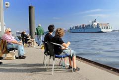 Schiffsanleger Hamburg Teufelsbrück - Menschen sitzen auf Stühlen in der Sonne und beobachten den Schiffsverkehr auf der Elbe.