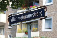 Strassenschild Mümmelmannsberg Balkons mit Blumen.