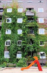 Spielplatz im Innenhof des Otto Stolten Gebäudes - die Fassade ist mit Kletterpflanzen bewachsen.