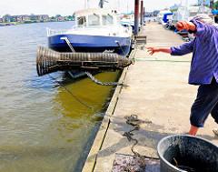 Mit Schwung wirft der Fischer die geleerte Metallreuse wieder in das Wasser der Billwerder Bucht.