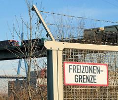 Zollzaun mit Schild Freizonengrenze - im Hintergrund Lastwagen auf der Köhlbrandbrücke, eines der Hamburger Wahrzeichen.