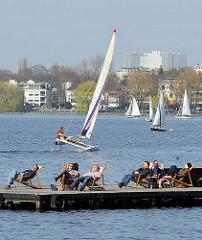 Frühling in Hamburg - die HamburgerInnen geniessen die Frühlingssonne in Liegestühlen am Bootssteg der Aussenalster. Im Hintergrund ein Katamaran in Fahrt.