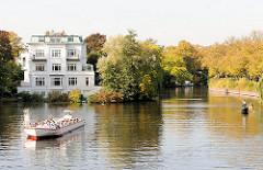Alstercabrio auf der Alster hinter der Krugkoppelbrücke - das Fahrgastschiff wendet und fährt zurück in die gestaute Alster - im Hintergrund eine Villa am Alsterufer und der Alsterkanal mit Herbstbäumen.
