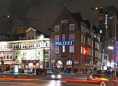 Spielbudenplatz und Polizeiwache an der Davidstrasse auf Hamburg St. Pauli - Nachtaufnahme mit fahrenden Autos.