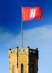 Die Hamburg Fahne flattert im Wind auf dem Turm der Alten Post.