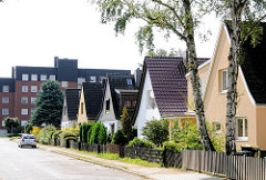 Einfamilienhäuser in gleichen Baustil - Spitzdachgebäude in Hamburg Wandsbek - Wohnblock im Hintergrund.