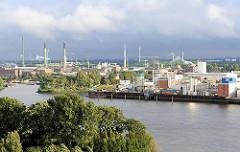 Fotos von dem Hamburger Stadtteil Veddel - Industriegebiet an der Elbe, Industriegebäude und hohe Schornsteine gegen dunklen Regenhimmel.