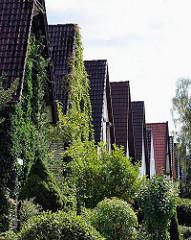 Einzelhäuser mit Satteldach - grüner Vorgarten im Weddinger Weg in Hamburg Rahlstedt.