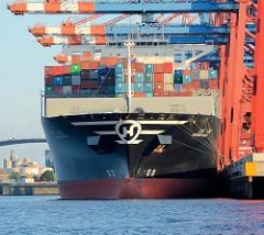 Containerfrachter Hanjin Gold unter den Containerbrücken des Containerterminals Eurogate im Hamburger Hafen - Schiffsbug, gestapelte Container / Stahlkisten.