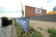 Schild Grasbrookhafen an der Einfahrt zum Hafenbecken - im Hintergrund der Kaispeicher A mit seinen markanten Hafenkränen an der Wasserseite des Kais. (2006)