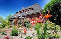 Backsteinhaus mit blühenden Blumen im Vorgarten - Einzelhaus in Hamburg Wilstorf.
