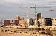 Entstehung der Hamburger Hafencity am Kaiserkai des Sandtorhafens. Hohe Baukräne stehen zwischen den entstehenden modernen Wohngebäuden. Im Vordergrund das Hafenbecken des Grasbrookhafens. 2006