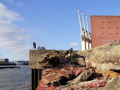 Kaimauer am Grasbrookhafen; drei Hafenkrane stehen auf der Wasserseite des Kaispeichers.