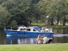 Polizeiboot auf der kanalisierten Alster, der Grenze zum Stadtteil Winterhude und Eppendorf. Ein Pärchen mit Hund sitzt am Winterhuder Ufer der Alster.