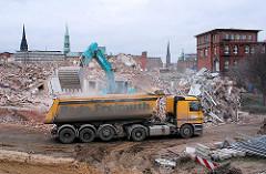 Ein Bagger lädt den Schutt der abgerissenen Gebäude auf einen Laster - rechts ein historisches Ziegelgebäude des Hafenamts. 2007
