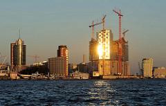 Bilder aus dem Hamburger Stadtteil Hafencity - Baustelle der Elbphilharmonie im Sonnenuntergang.