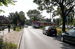 Vorortsbahn - AKN Bahn kreuzt die HolsteinerChaussee. Autos warten vor der Bahnschranke, der Zug fährt in die Haltestelle Burgwedel ein.