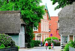 Dorfstrasse in Hamburg Curslack - historische Häuser am Strassenrand; Fahrradfahrerin.
