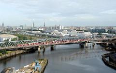 Blick über den Billhafen zum Oberhafenkanal - ein S-Bahnzug überquert die Eisenbahnbrücke; dahinter die Architektur der Gemüsehallen im Hamburger Stadtteil Hammerbrook.