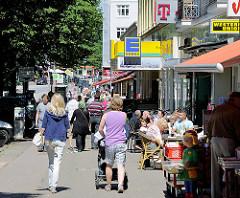 Geschäfte und Passanten - Fuhlsbüttler Strasse; Kaffee mit Tischen auf dem Fussweg - Motive aus dem Hamburger Stadtteil Barmbek Nord.