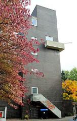 Kirchturm der Dietrich Bonhoeffer Kirche in Hamburg Dulsberg Süd - Backsteinkirche / Ziegelfassade; Herbstbaum mit roten Blättern.
