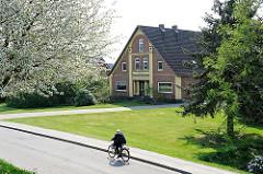 Radfahrer in der Sonne - Bauernhaus; blühender Kirschbaum am Deich von Hamburg Neuenfelde.