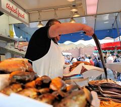 Fischstand auf dem Altonaer Fischmarkt in Hamburg - Räucherfisch liegt zum Verkauf aus - der Verkäufer preist einen großen geräucherten Aal an.