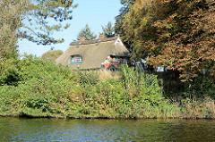 Reetdachhaus am Ufer der Doveelbe in Hamburg Allermöhe - Radfahrerin auf dem Deich.