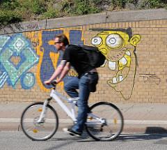 Graffiti auf einer Ziegelwand - Radfahrer auf der Strasse.