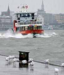 Hafenfähre Hamburgensie vor dem Anleger Altonaer Fischmarkt - die Gischt sprüht am Bug hoch auf. Möwen ruhen sich auf dem Anleger beim Sturm aus.
