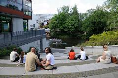 Treppen zum Goldbekkanal - Kanus auf dem Kanal. Angestellte machen ihre Mittagspause in der Sonne am Wasser.