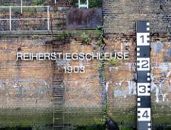 Mauer Reiherstiegschleuse, erbaut 1903; eine rostige Eisenleiter führt ins Wasser - rechts kann die Durchfahrtshöhe bei der Einfahrt in die Schlickschleuse abgelesen werden, die je nach Tide variiert.