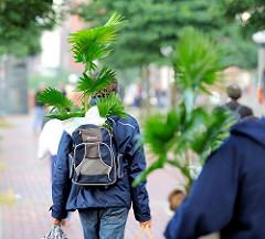 Abtransport von auf dem Fischmarkt in Hamburg Altona gekaufte Grünpflanzen - ein Marktbesucher hat seine neue Palme in den Rucksack gesteckt - ein anderer Trägt die Pflanze im Arm.