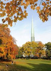 Herbst in Hamburg - Bäume mit herbstlichen Blättern / Herbstkleid beim Simon Bolivar Park - im Hintergrund die Hamburger St. Nikolaikirche in Harvestehude.