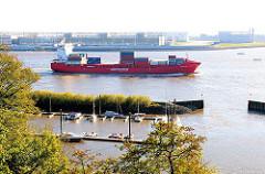 Ein Feederschiff hat den Hamburger Hafen verlässen und fährt auf der Elbe stromabwärts - im Vordergründ der Mühlenberger Yachthafen. Am anderen Ufer der Elbe das Airbusgelände.