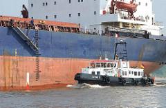 Ein Lotsenboot fährt längsseits eines Frachters auf der Elbe; die Gangway wird für den Lotsen herunter gelassen.