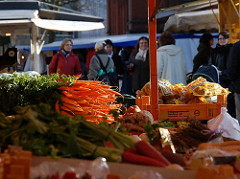Gemüsestand auf dem Eimsbüttler Wochenmarkt - ein Bund Möhren leuchtet in de Sonne.