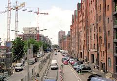 Baubetrieb am Sandtorkai - Baukräne stehen am Sandtorhafen, die neuen Gebäude der Hafencity wachsen. Rechts die Backsteinfassaden der Speicher im ehemaligen Hamburger Freihafen. (2004)