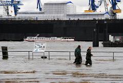 Hochwasser in Hamburg - Sturmflut am Altoner Fischmarkt - Arbeitskräfte in Wathosen gehen durch das Wasser - im Hintergrund ein Boot der Hafenrundfahrt.