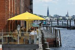 Aussengastronomie an der Elbe - Gäste sitzen auf der Terrasse am Wasser - im Hintergrund der Anleger Altoner Fischmarkt und das Panorama Hamburgs.