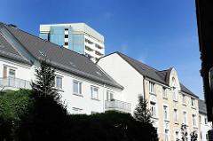 Wohngebäude unterschiedlicher Stilrichtungen in Hamburg Sankt Pauli. Ein Hochhaus hinter den Dächern von mehrstöckigen Wohngebäuden.
