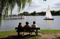 Drei Besucherinnen des Alsterufers sitzen auf einer Parkbank und blicken auf die Aussenalster - ein Alsterschiff und Segelboot fahren vorüber.