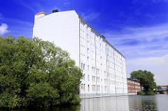 Mehrstöckiges weisses Gewerbegebäude direkt am Kanalufer in Hamburg Hamm.