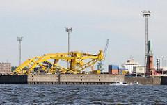 Gesprengte gelbe Kräne - die Hafenkräne sind umgestürzt und liegen quer auf dem Kronprinzenkai des Kaiser Wilhelm Hafens - eine Barkasse der Hamburger Hafenrundfahrt fährt auf ihrem Törn Richtung Norderelbe.