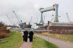 Passanten auf dem Deich in Hamburg Neuenfelde - Portalkran auf dem Werftgelände der Sietas Werft.