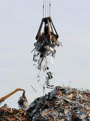 Schrottumschlag im Hamburger Hafen - von einem Berg Altmetall hat ein Kran mit einem Greifer Altes Eisen und Metall aufgenommen.