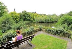 Parkfriedhof Hamburg Ohlsdorf - eine Parkbesucherinn liest in einem Buch auf einer Bank an einem See.