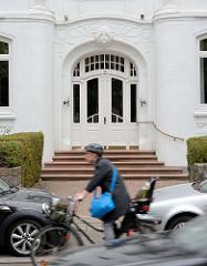 Eingang Wohnhaus Sierichstrasse - Jugendstildekor  über der Eingangstür. Fahrradfahrerin mit Helm in Fahrt.