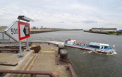 Eine Barkasse mit Touristen an Bord kommt aus dem Magdeburger Hafen und läuft in die Norderelbe ein - im Hintergrund das Hafenbecken des Baakenhafens mit Versmannkai und Petersenkai. (2007)
